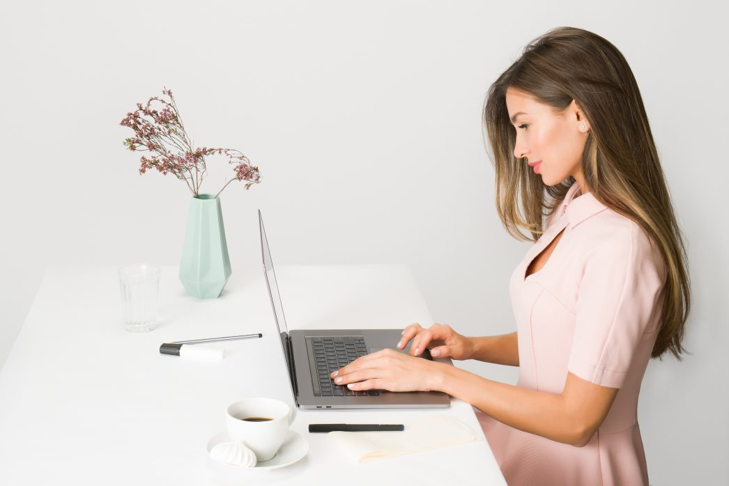 Woman in a pink dress typing on a laptop