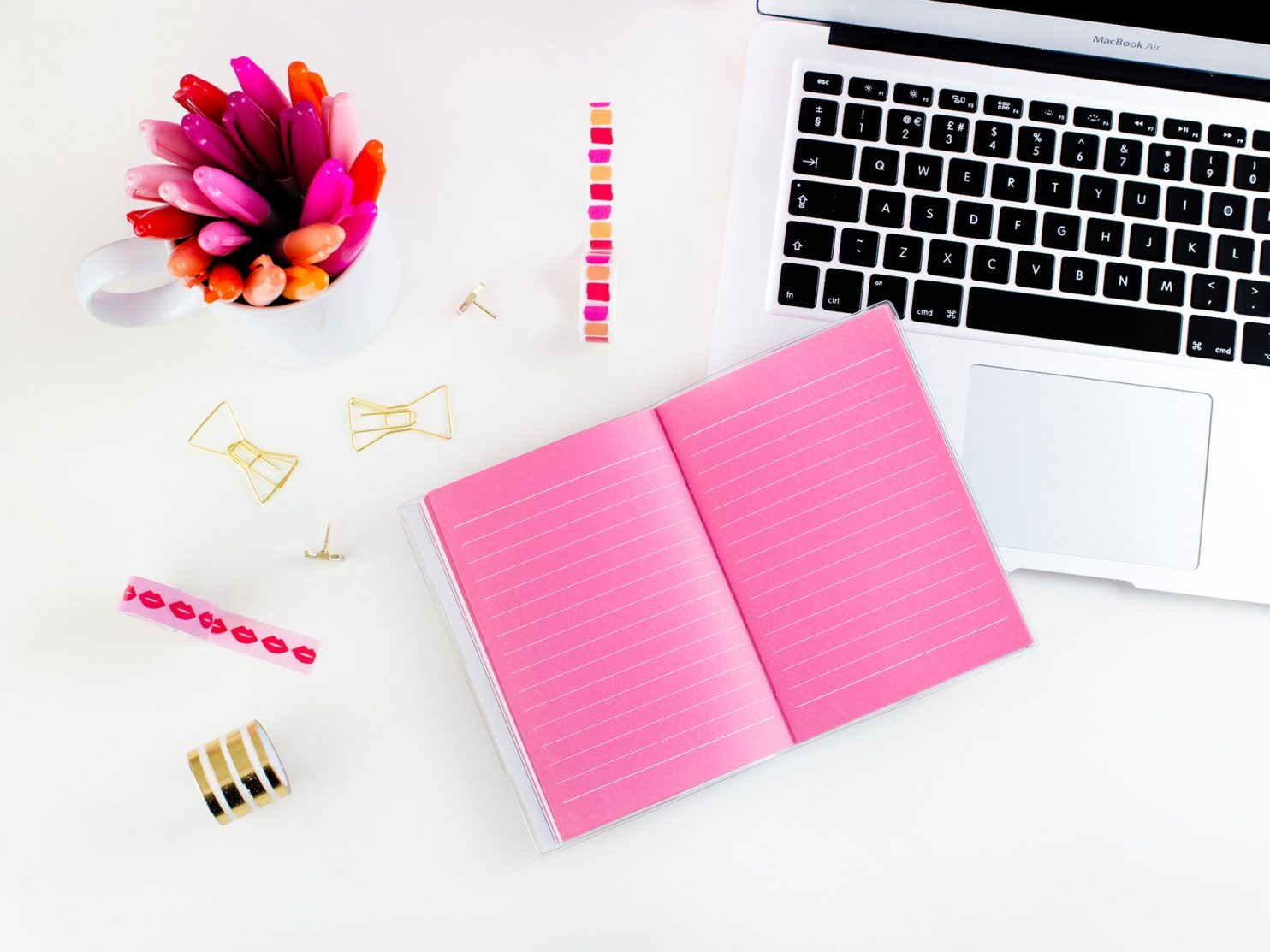 An open notebook with bright pink pages that's placed on top of a white laptop and next to a pot of pink pens