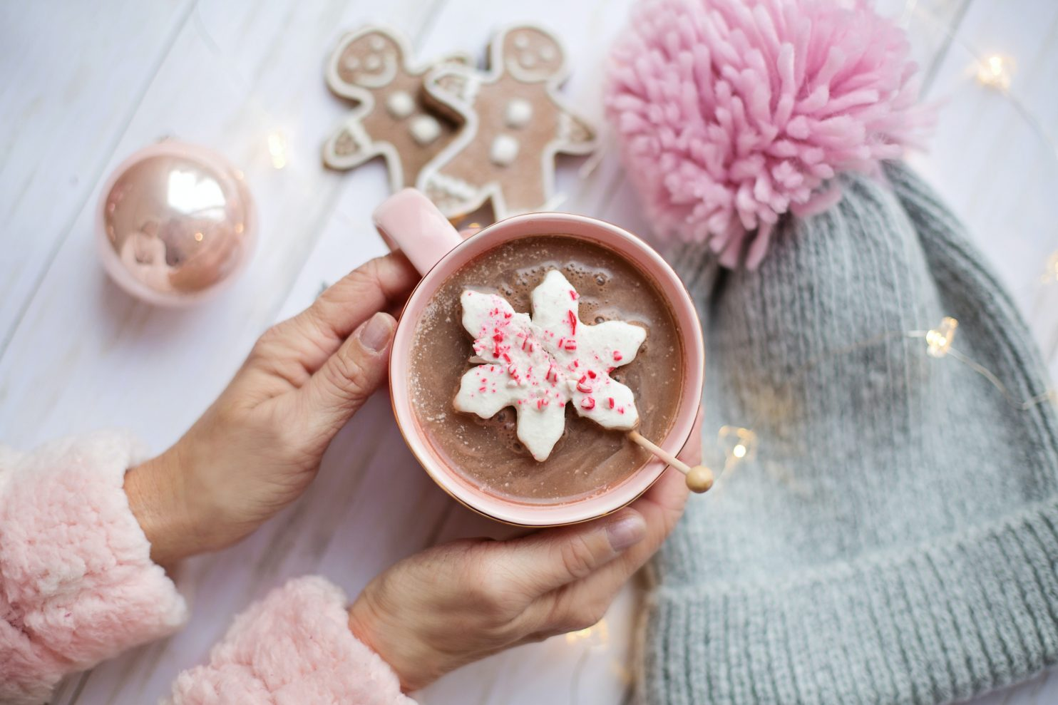 Someone holding a hot chocolate with gingerbread cookies near the mug