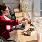 A woman in wheelchair using a laptop