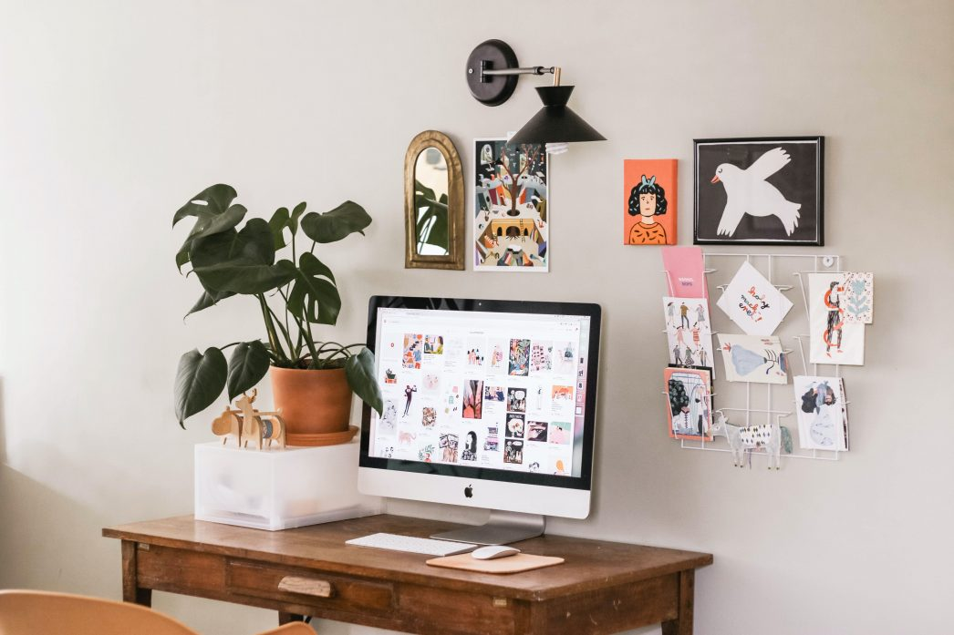A computer and potted plant on a desk. There's lots of artwork on the wall around the desk