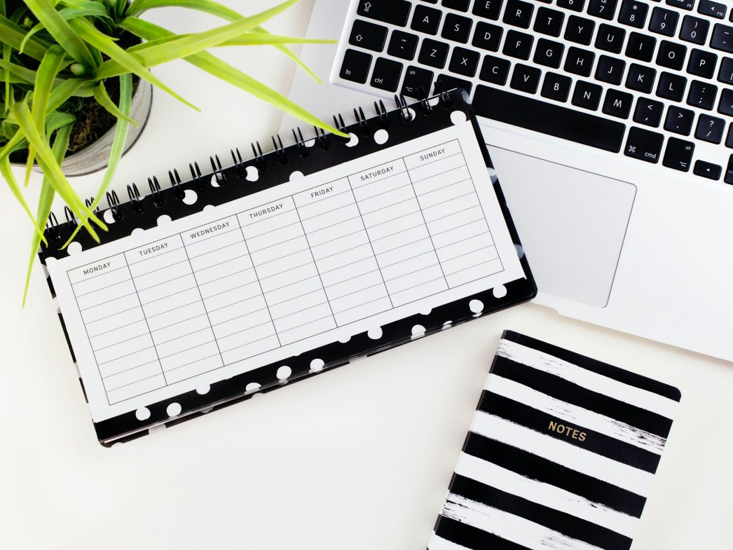 A black-and-white desk planner next to a notebook, laptop and plant