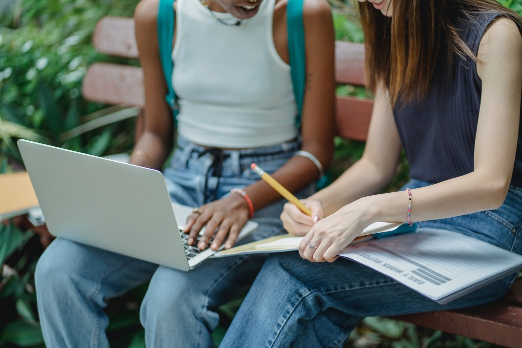 Two students on a bench. One has a laptop and the other, a notebook