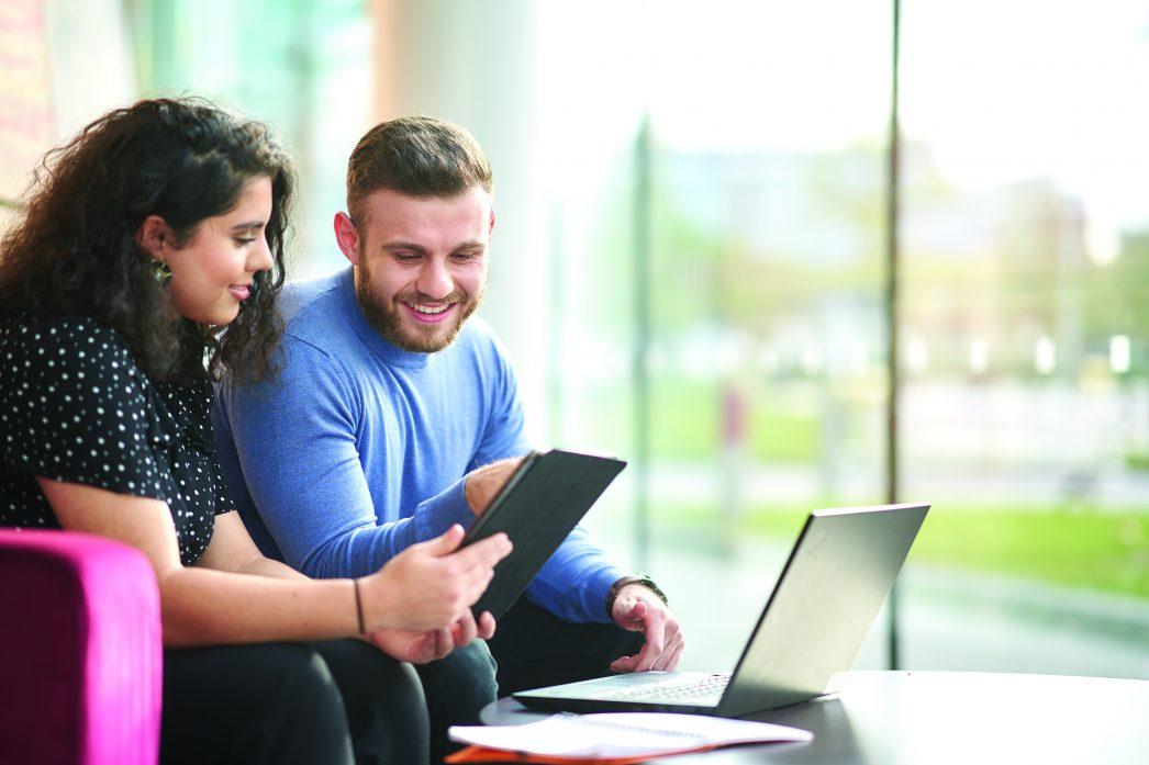 Two students on campus looking at something on a tablet