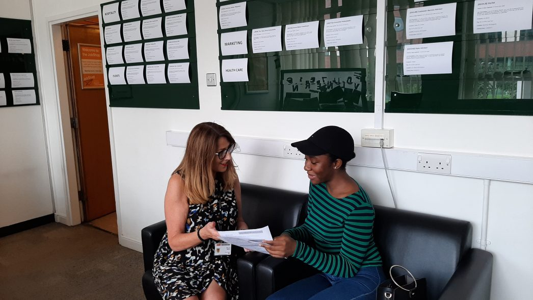 A student getting CV advice from Cathy, the JobShop manager