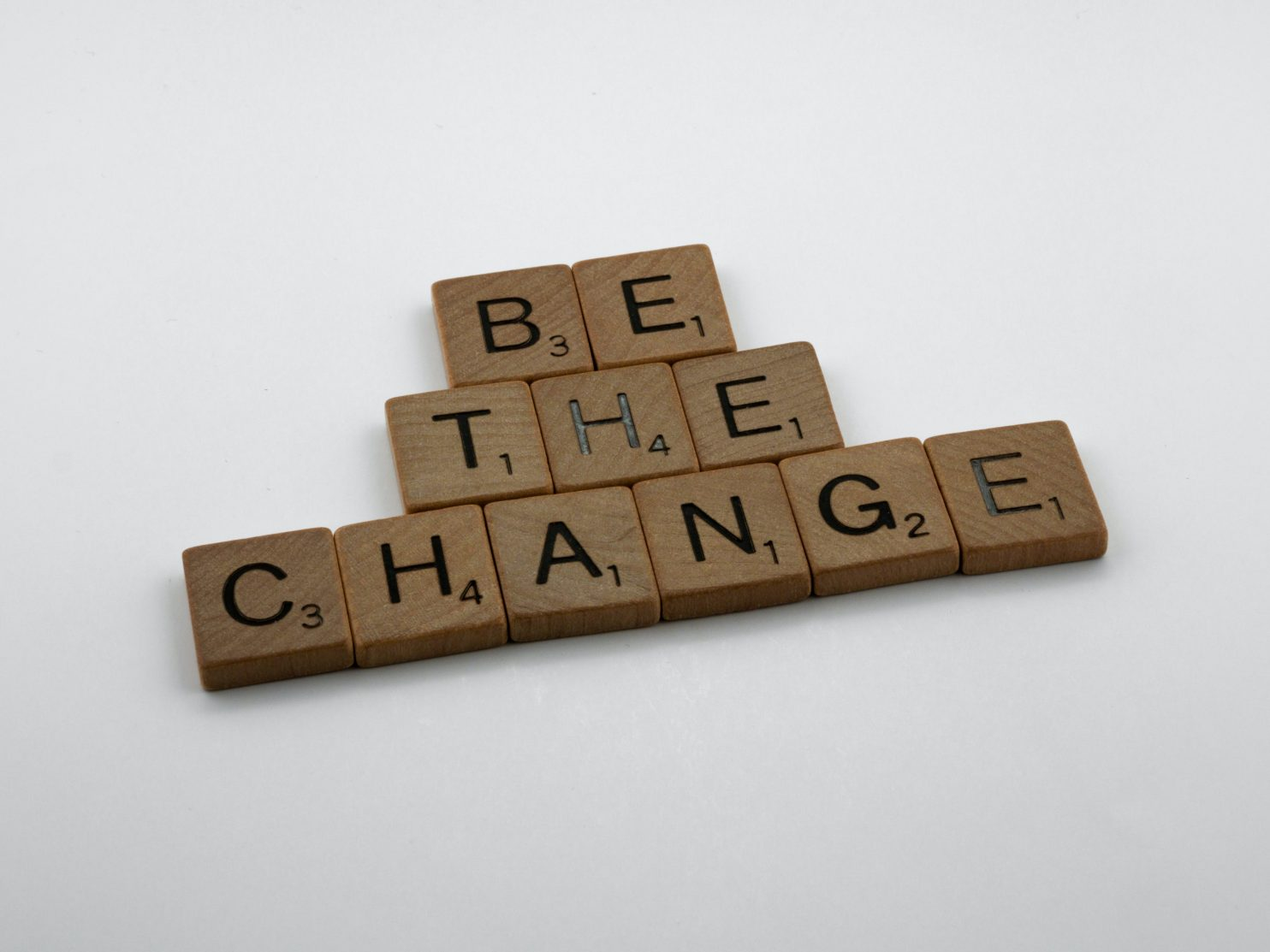 Wooden blocks on a white background that spell out 'Be the change'