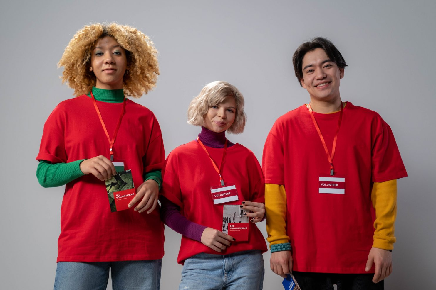 Three volunteers in bright red shirts looking at the camera