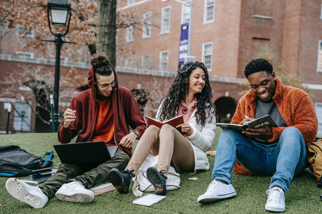 A group of students sitting outside on some grass, looking at books and laughing