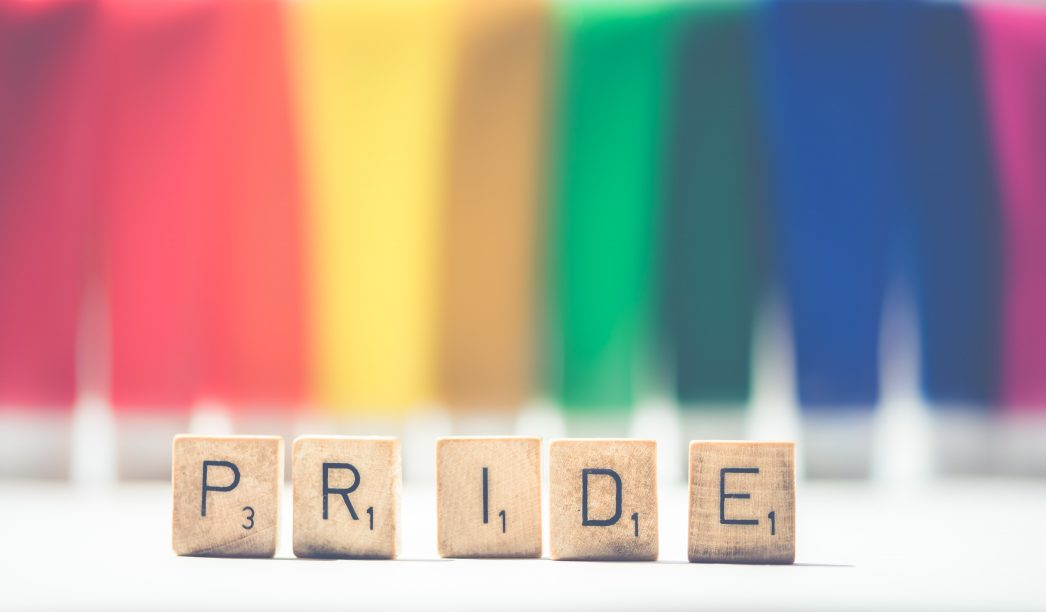 Scrabble tiles that spell out 'Pride' stand in front of a rainbow backdrop