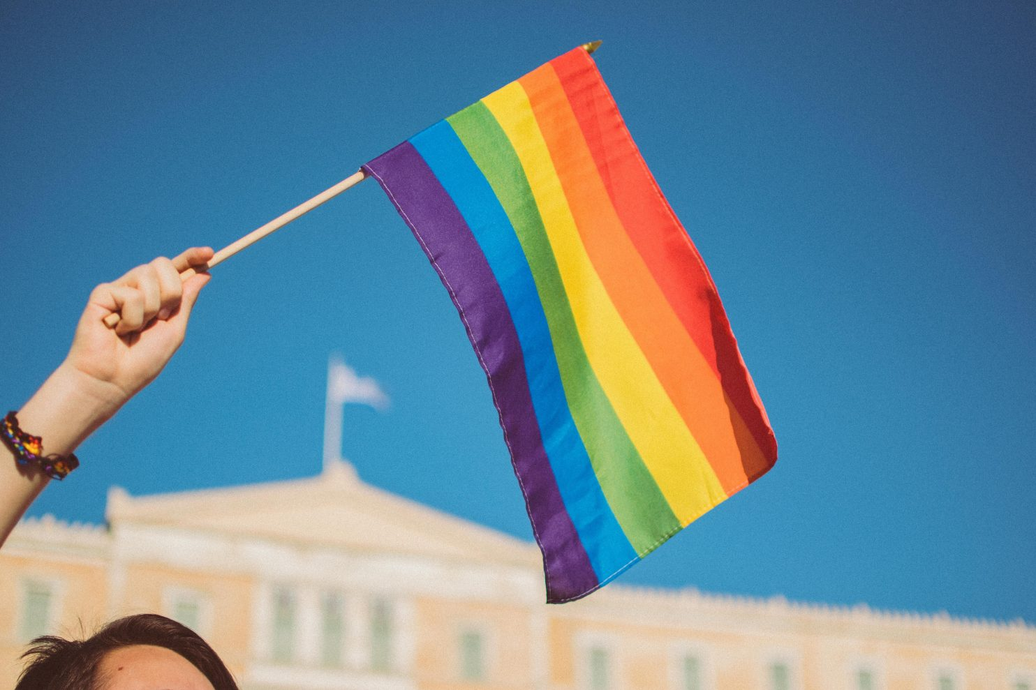 Someone is waving the Pride flag against a blue sky